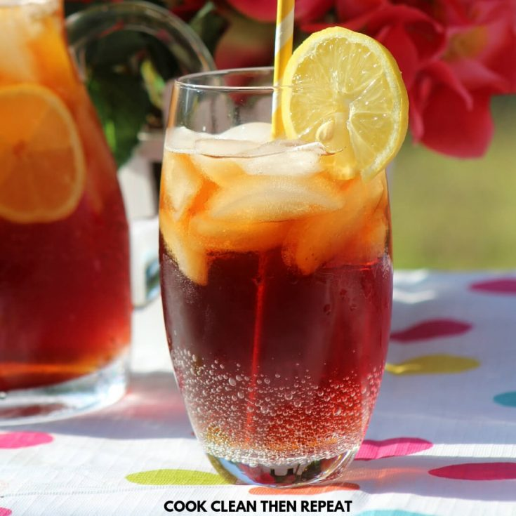 Sweet tea in a glass with a lemon slice and flowers in the background with polka dot table cloth underneath.