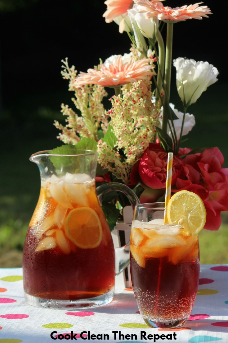 Sweet tea in a pitcher on a table with a glass next to it with some sweet tea and ice in it with a lemon slice and a yellow and white paper straw. Flowers in the background.