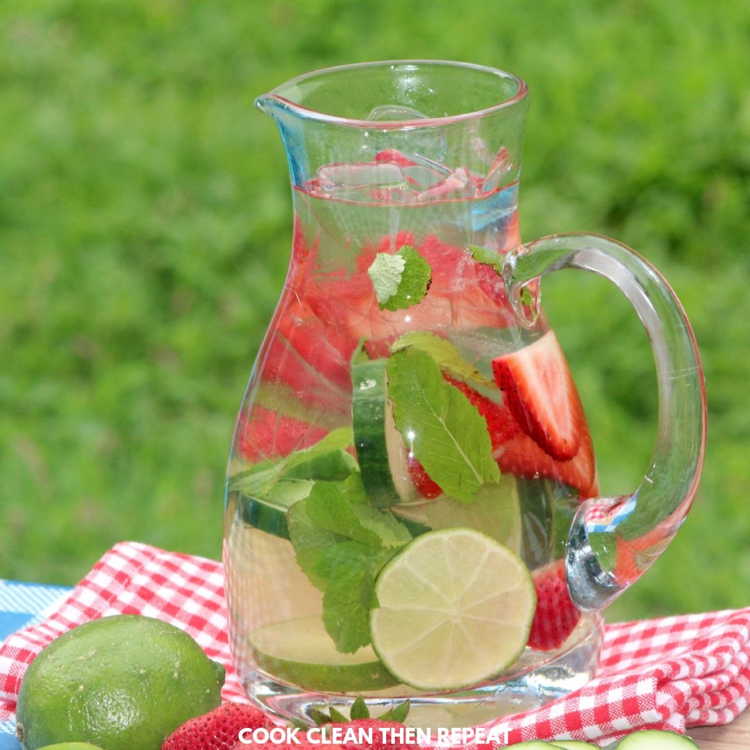 An image of a pitcher of water with fruit and herbs inside.
