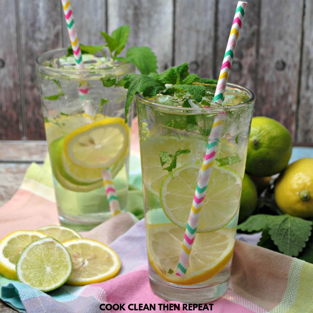 Two glass cups with water inside with ice, paper straws, and lemon and lime slices inside. Table cloth on the table is pink, green, blue, plaid.