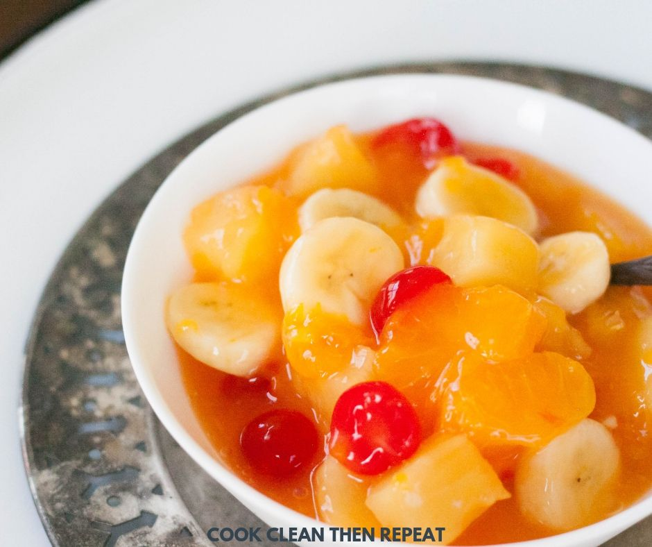 square photo of finished fruit salad in a white bowl with a silver spoon in it.