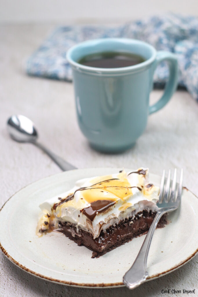 A slice of the finished no bake chocolate pudding cake recipe ready to eat with a cup of coffee in the background.