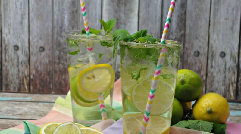 Two glasses of lemon water with leaves, lemons, limes, sliced included.