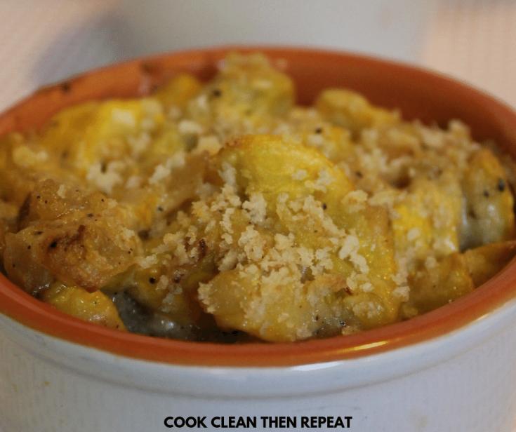 Serving of yellow squash recipe in a dish. Summer squash casserole in a white dish with orange interior.