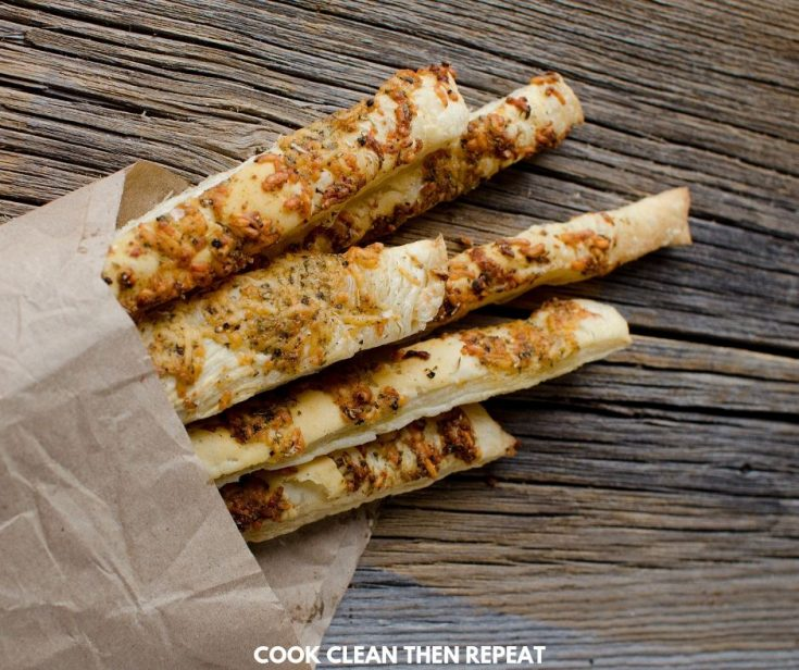 Breadsticks ready to eat wrapped in brown paper.