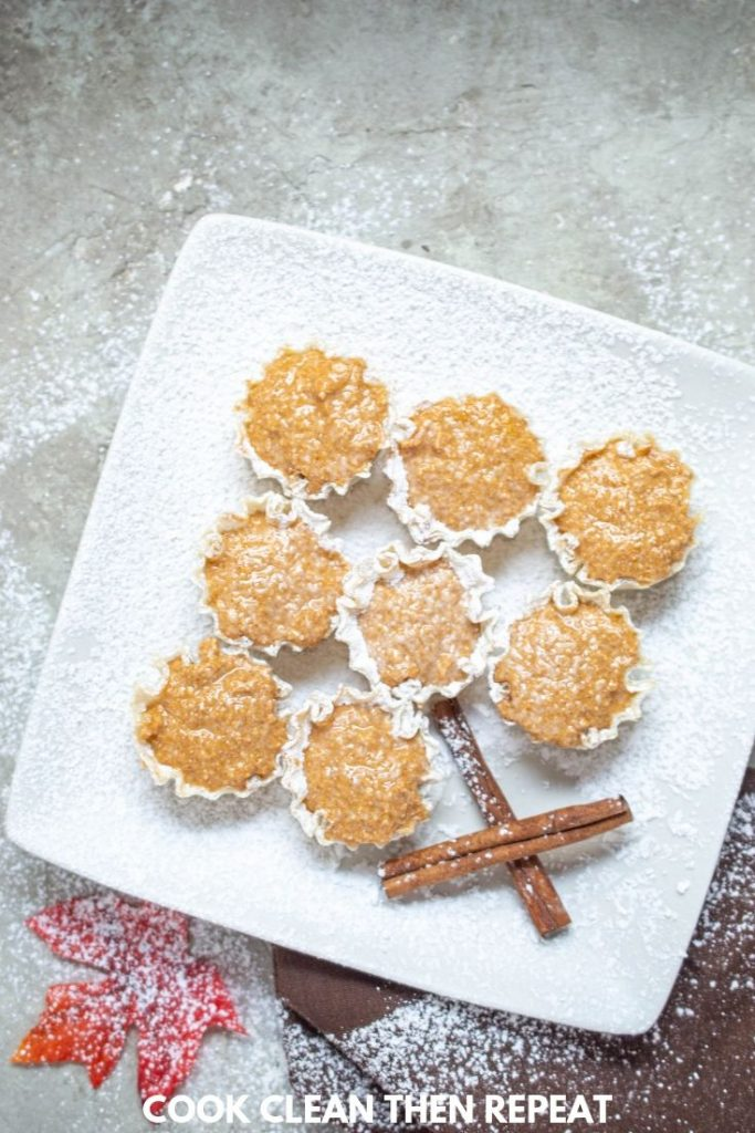 Finished pie bites on a plate dusted with powdered sugar.