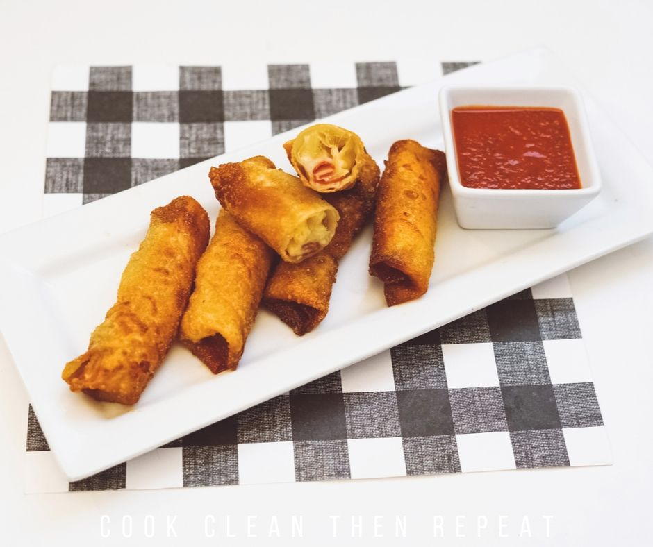 shot of the finished pizza egg rolls with dipping sauce.