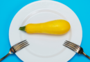 Featured image showing a cleaned yellow squash on a plate ready to be prepared.