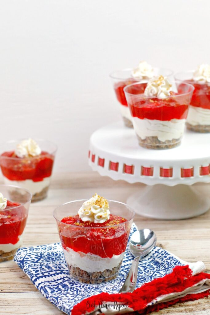 Here we see a variety of strawberry jello cheesecake cups set out and ready to be served.