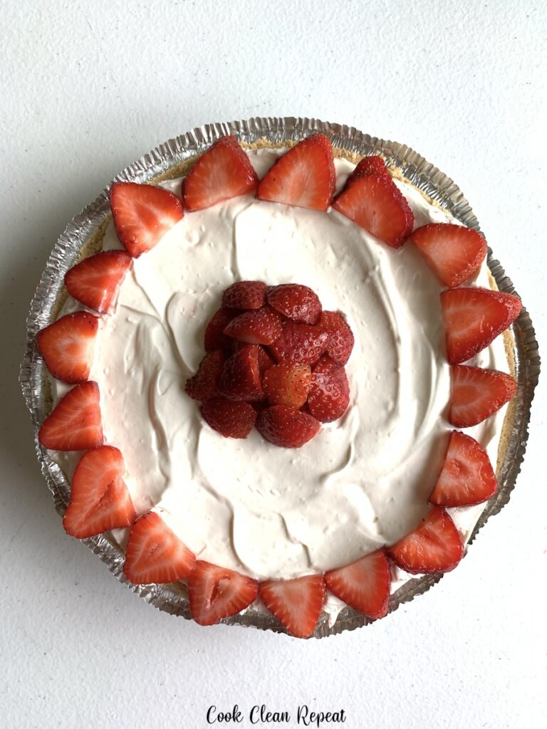 A top down look at the finished and decorated no bake strawberry cheesecake.