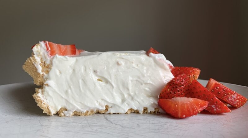 Featured image showing a single slice of the no bake strawberry cheesecake on a plate ready to serve.