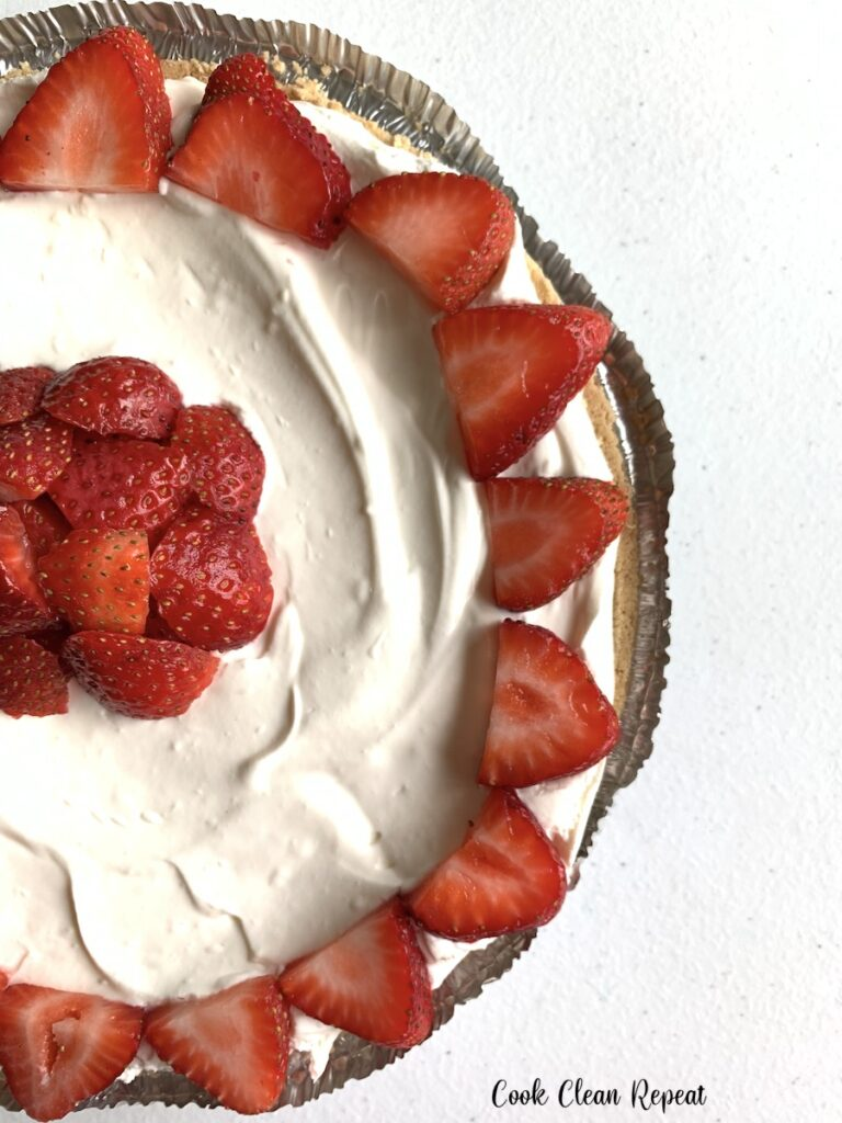 A full finished strawberry cheesecake ready to cut and serve.