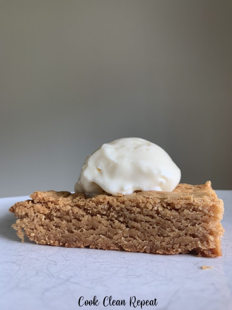 A close up view of the finished blondies on a plate ready to eat with ice cream on top.