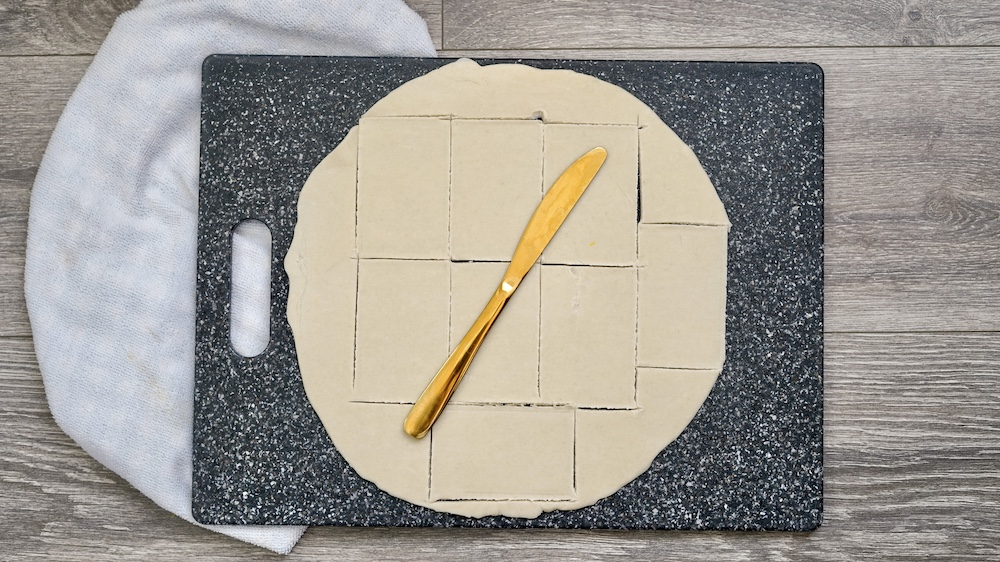 Dough being cut out into squares.