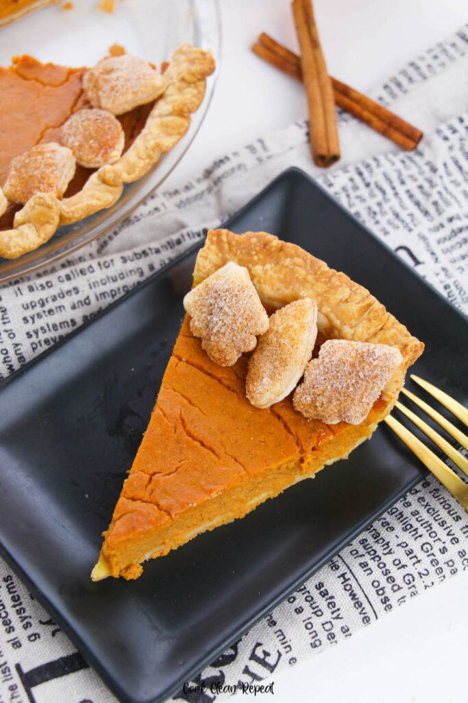 A top down view of a slice of baked pumpkin pie ready to eat.