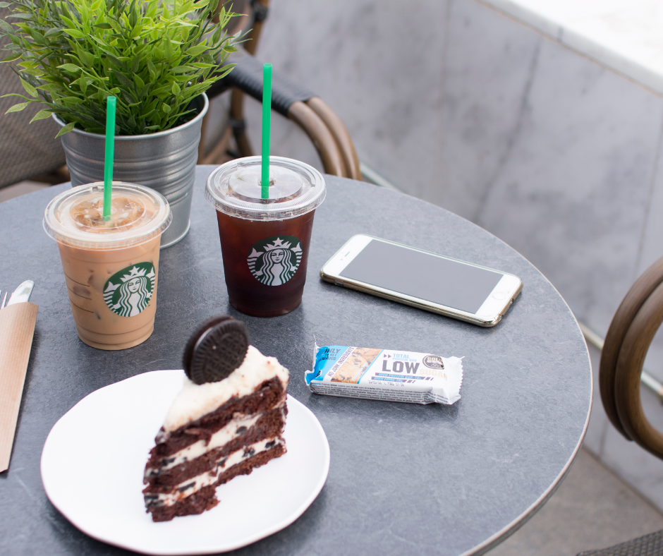 Some Starbucks coffee drinks with cake on a table by a phone.