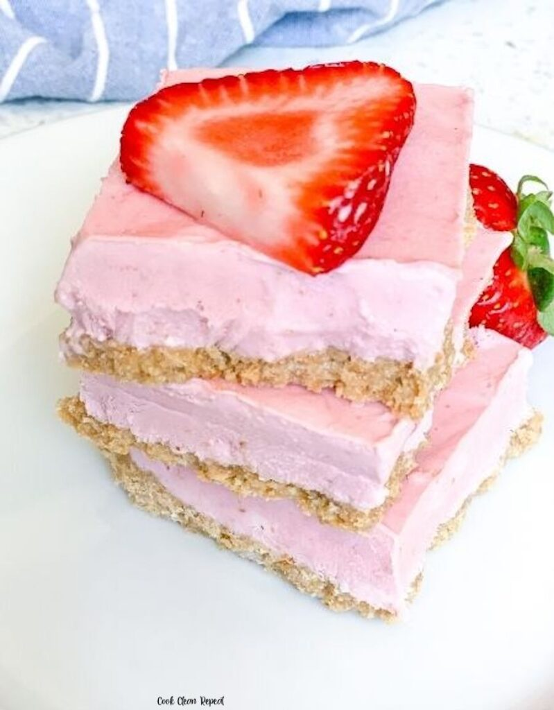 A stack of the finished strawberry cheesecake bars ready to eat.