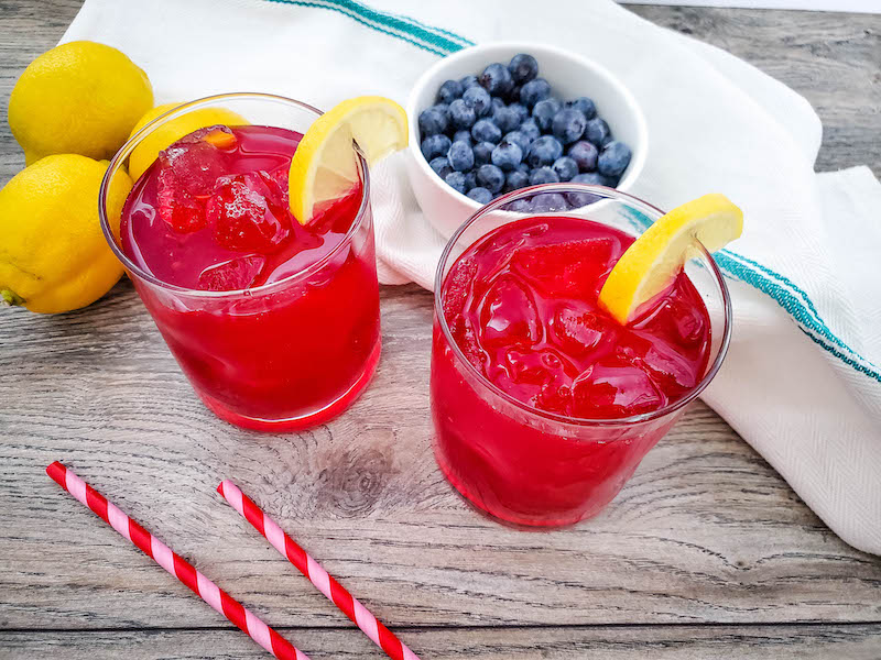 A look at a few glasses of blueberry lemonade ready to drink.