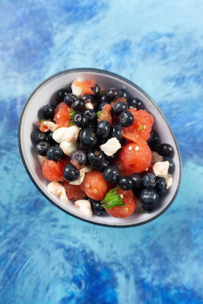 A top down look at the bowl full of the finished feta watermelon salad ready to eat.