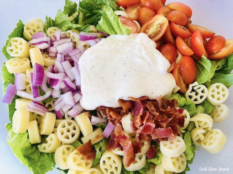Salad with pasta and dressing ready to be mixed.