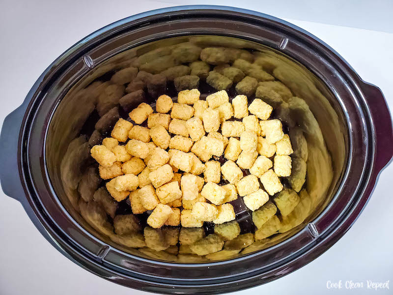 Crockpot interior with layer of tater tots on the bottom.