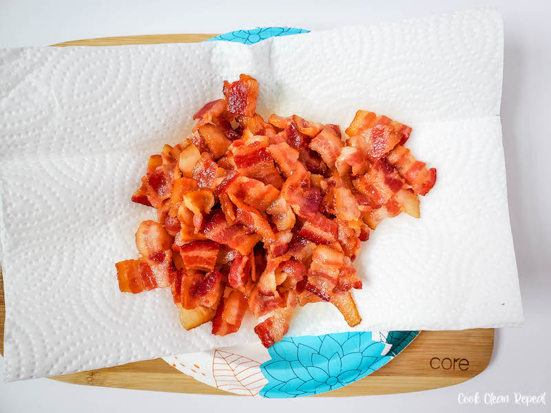 Cooked bacon draining on some paper towels on a plate.