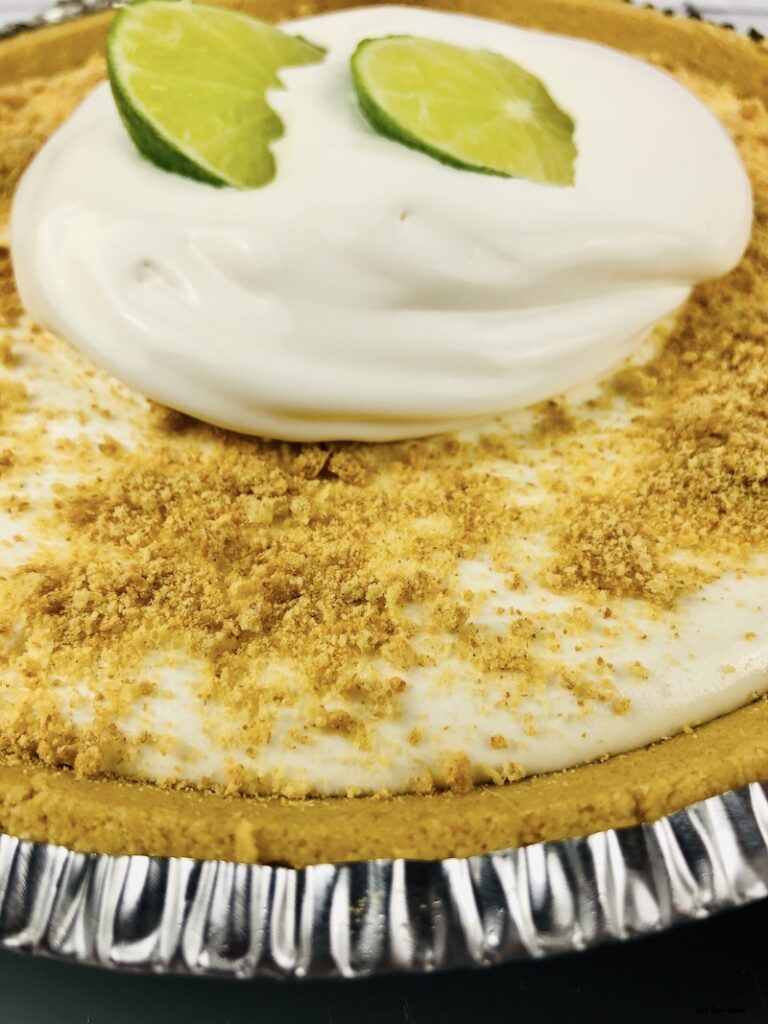 Full finished pie topped with graham crackers and whipped cream with limes.