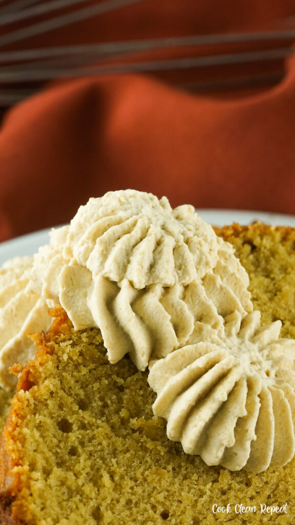 A close up of the finished whipped cream on a slice of pumpkin bread.