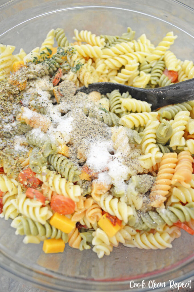 seasonings being added to the pasta.