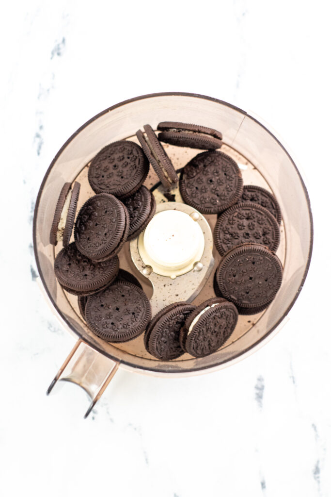 Oreo cookies In the food processor ready to be crushed.