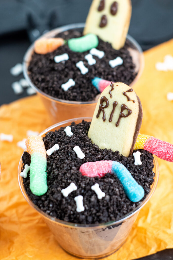 Decorating with worms and grave stone cookies for the final touches on the halloween dirt pudding dessert.