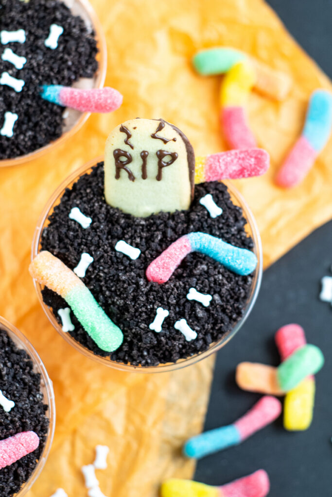 A top down look at the finished halloween dirt pudding cups with worms and gravestone ready to eat.