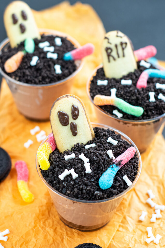 A variety of finished halloween dirt pudding dessert graveyard cups.