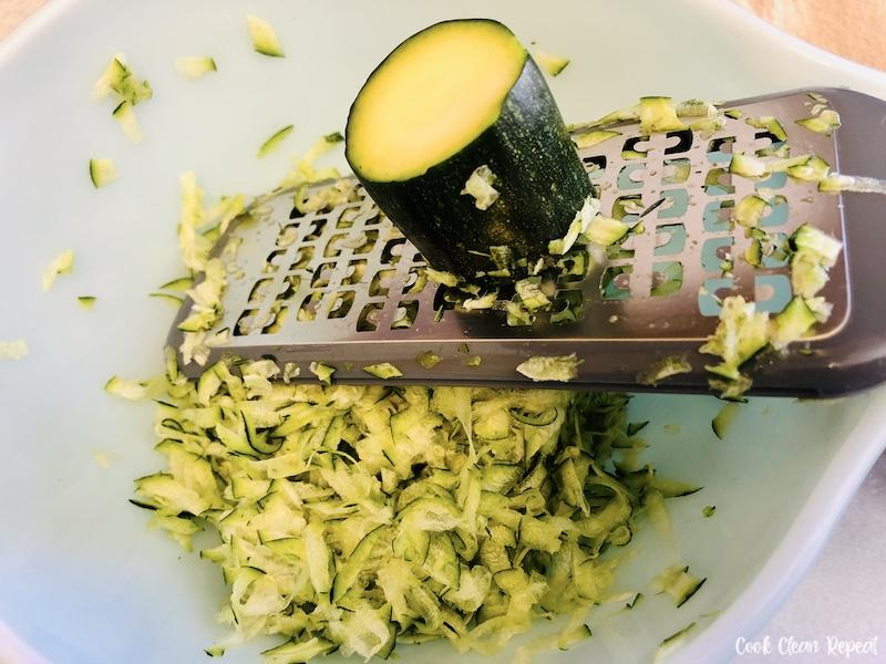 Shredding zucchini into a bowl.