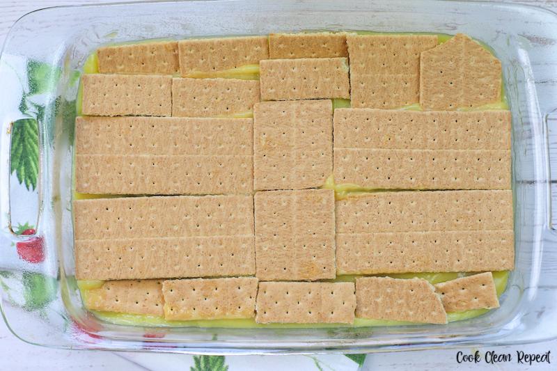 Second graham cracker layer being added.