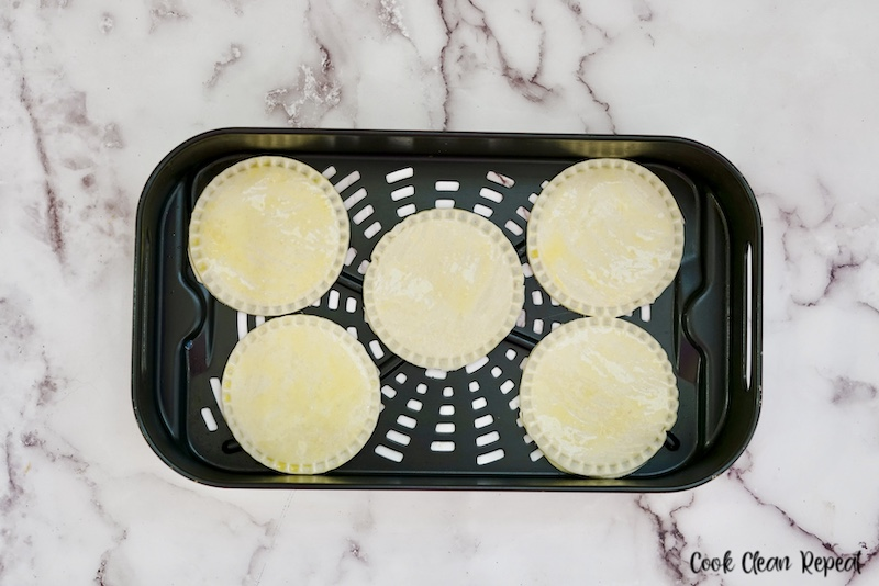 air fryer basket loaded with pies ready to bake.