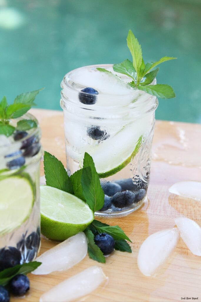 A look at a glass of the finished infused water recipe with blueberries and lime with mint.